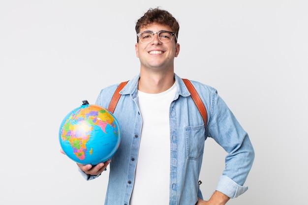 Junger gutaussehender mann, der glücklich mit einer hand auf der hüfte und selbstbewusst lächelt. student, der eine weltkugelkarte hält