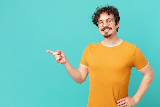 Junger gutaussehender mann, der glücklich mit einer hand auf der hüfte und selbstbewusst lächelt