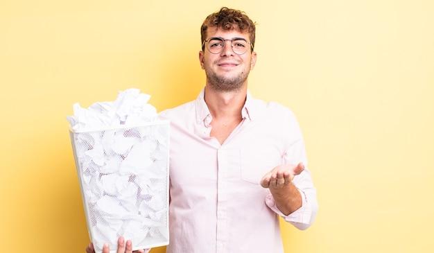 Junger gutaussehender mann, der glücklich mit freundlichem lächeln lächelt und ein konzept anbietet und zeigt. papierkugeln müllkonzept