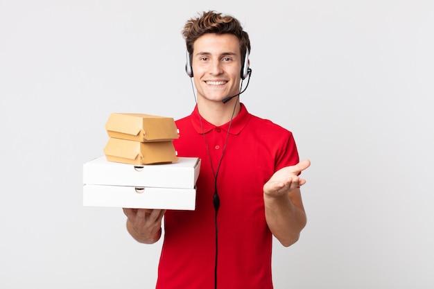 Junger gutaussehender mann, der glücklich mit freundlichem lächeln lächelt und ein konzept anbietet und zeigt. take-away-fast-food-konzept