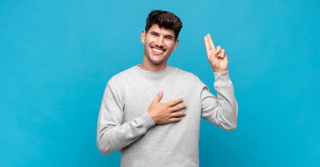 Junger gutaussehender mann, der glücklich, selbstbewusst und vertrauenswürdig aussieht, lächelt und ein siegeszeichen zeigt, mit einer positiven einstellung