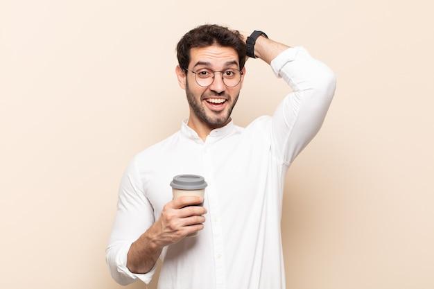 Junger gutaussehender mann, der glücklich, sorglos, freundlich und entspannt aussieht und das leben und den erfolg mit einer positiven einstellung genießt