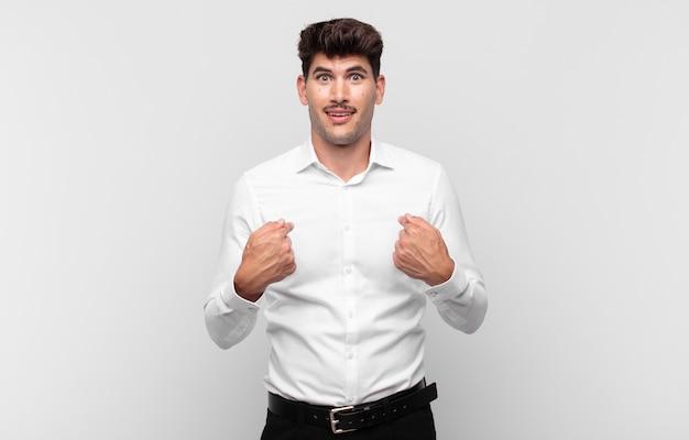 Junger gutaussehender mann, der glücklich, überrascht und stolz ist und mit einem aufgeregten, erstaunten blick auf sich selbst zeigt