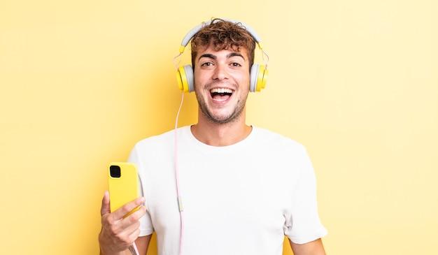 Junger gutaussehender mann, der glücklich und angenehm überrascht aussieht. kopfhörer- und smartphone-konzept