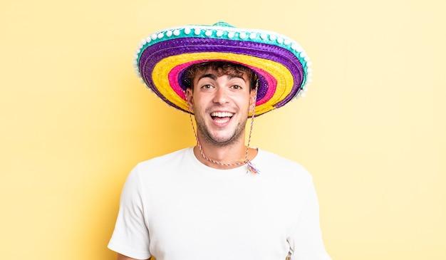 Junger gutaussehender mann, der glücklich und angenehm überrascht aussieht. mexikanisches hutkonzept