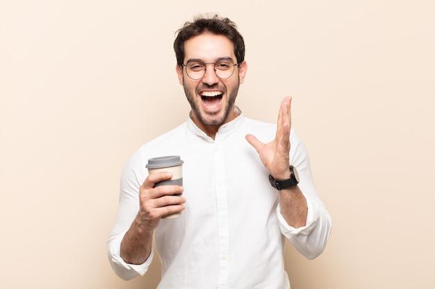 Junger gutaussehender mann, der glücklich und aufgeregt aussieht, schockiert mit einer unerwarteten überraschung mit beiden händen offen neben gesicht