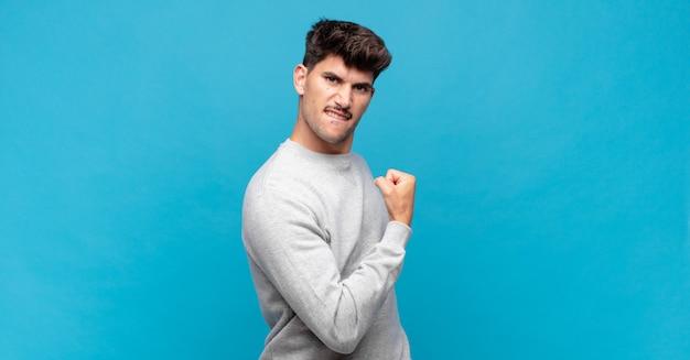 Junger gutaussehender mann, der glücklich, zufrieden und kraftvoll fühlt, passform und muskulösen bizeps, stark nach dem fitnessstudio schauend