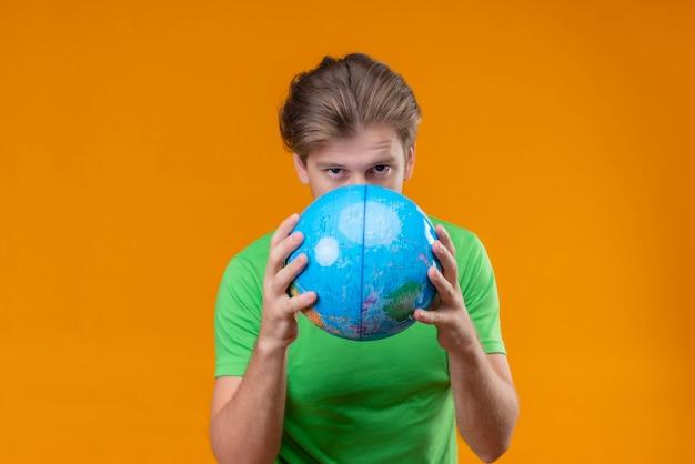 Junger gutaussehender mann, der grünes t-shirt hält, das globus hält, der sich hinter ihm mit ernstem gesicht hält, das über orange wand steht