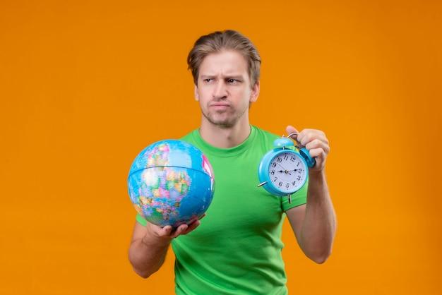 Junger gutaussehender mann, der grünes t-shirt hält, das globus und wecker hält, der beiseite schaut mit dem stirnrunzeln missfiel, das über orange wand steht