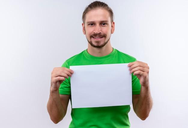 Junger gutaussehender mann, der grünes t-shirt hält, das leeres papier hält, das die kamera sieht, die zuversichtlich weiß, über weißem hintergrund steht