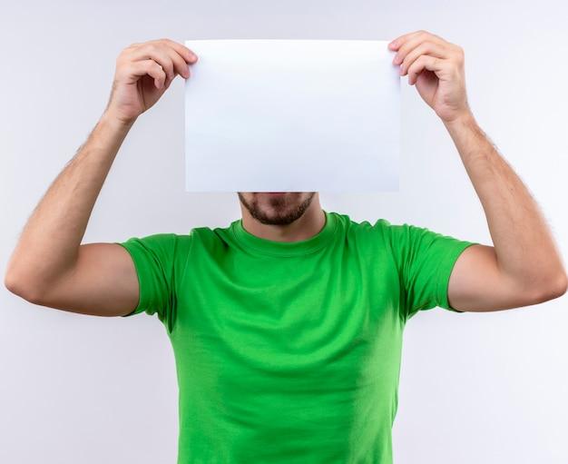 Junger gutaussehender mann, der grünes t-shirt hält, das leeres papier hält, das sich dahinter versteckt über weißem hintergrund