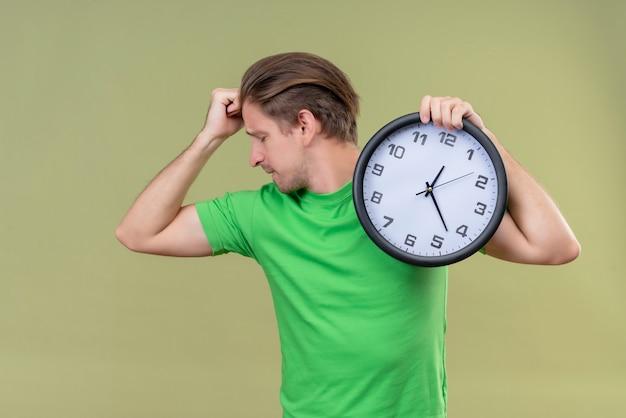 Junger gutaussehender mann, der grünes t-shirt hält uhr hält, das bizeps zeigt, der über grüner wand steht