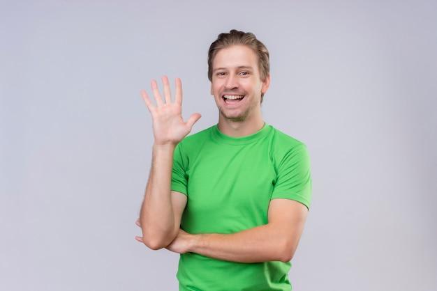 Junger gutaussehender mann, der grünes t-shirt trägt, das mit hand steht, die über weißer wand steht