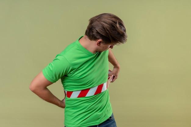Junger gutaussehender mann, der grünes t-shirt unter verwendung des klebebandes im sicheren stehen über grüner wand 2 trägt