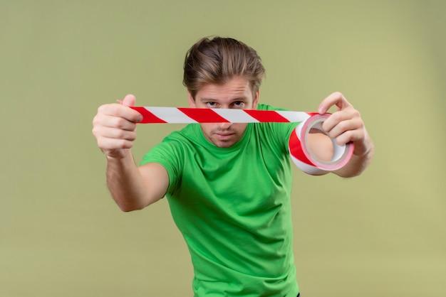 Junger gutaussehender mann, der grünes t-shirt unter verwendung des klebebandes im sicheren stehen über grüner wand 3 trägt