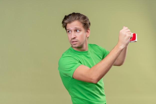 Junger gutaussehender mann, der grünes t-shirt unter verwendung des klebebandes im sicheren stehen über grüner wand 5 trägt