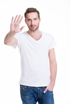 Junger gutaussehender mann, der halt mit seiner hand benötigt - isoliert auf weiß