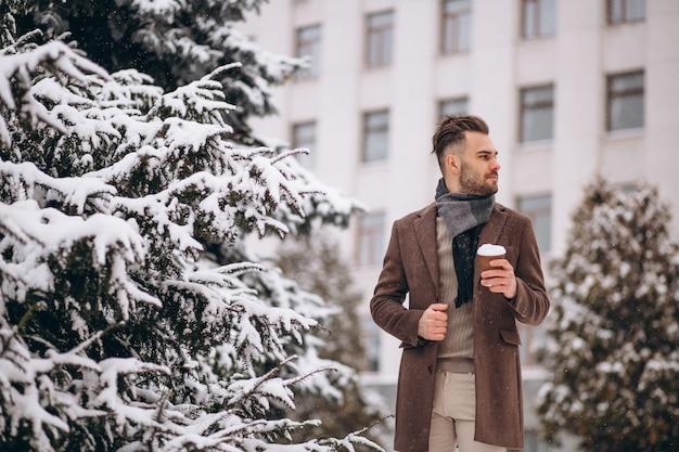 Junger gutaussehender mann, der heißen kaffee draußen an einem wintertag trinkt