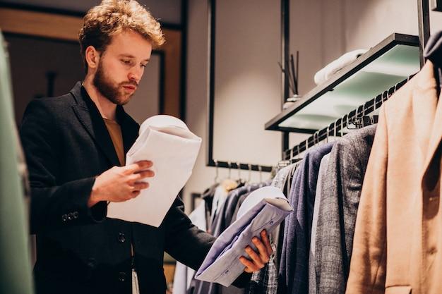 Junger gutaussehender mann, der hemd an einem shop wählt
