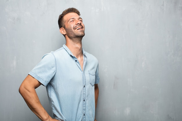 Junger gutaussehender mann, der heraus mit dem kopf rückwärts gekippt und glücklich, heiterer ausdruck heraus lacht