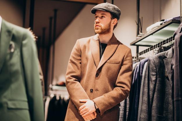 Junger gutaussehender mann, der hut am shop wählt
