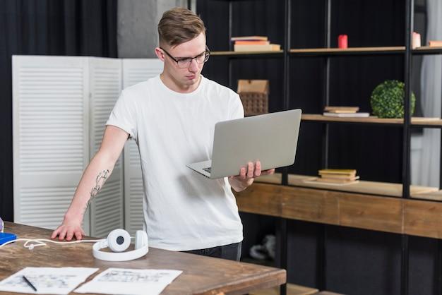 Junger gutaussehender mann, der in der hand laptop betrachtet