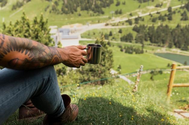 Junger gutaussehender mann, der in die berge reist