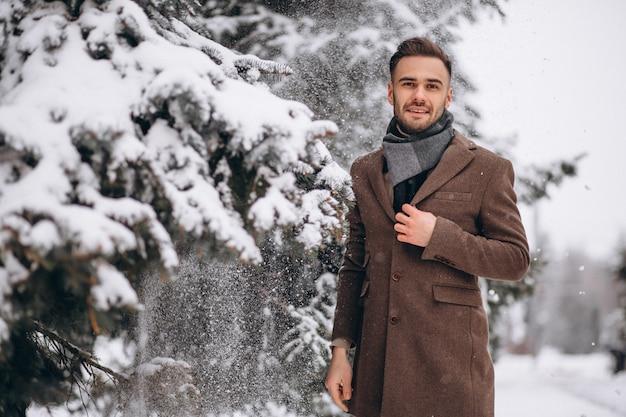 Junger gutaussehender mann, der in einen winterwald geht