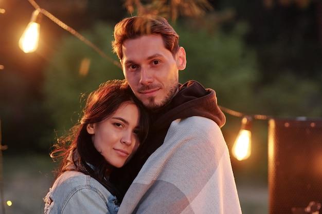Junger gutaussehender mann, der in plaid gewickelt ist und seine hübsche freundin umarmt, während beide abends im freien gegen lichter ruhen
