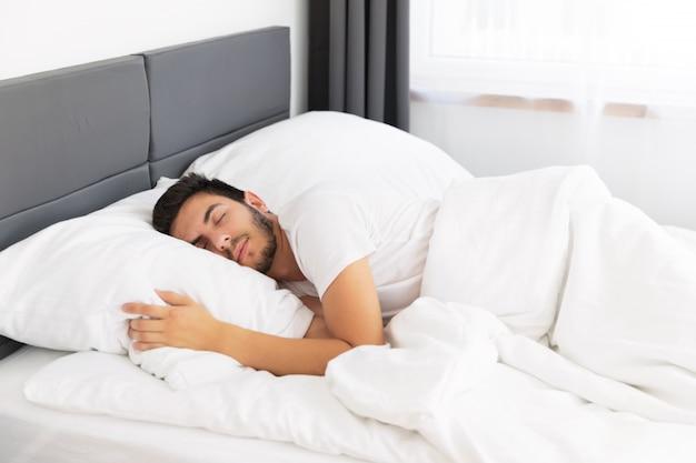 Junger gutaussehender mann, der in seinem bett schläft.