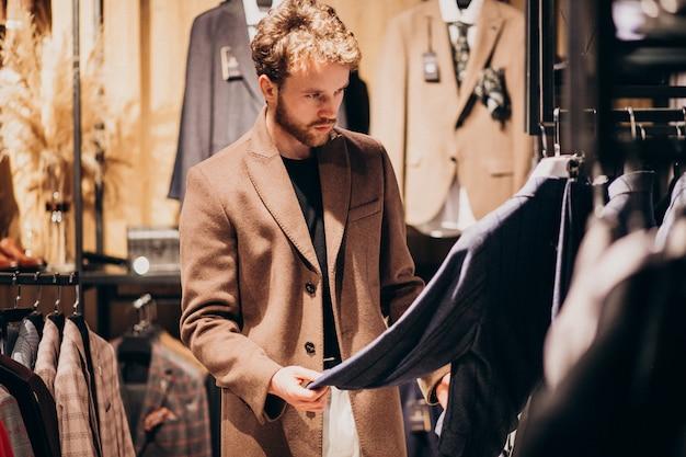 Junger gutaussehender mann, der kleidung am shop wählt