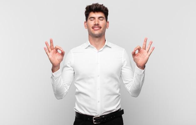 Junger gutaussehender mann, der konzentriert und meditierend aussieht, sich zufrieden und entspannt fühlt, denkt oder eine wahl trifft
