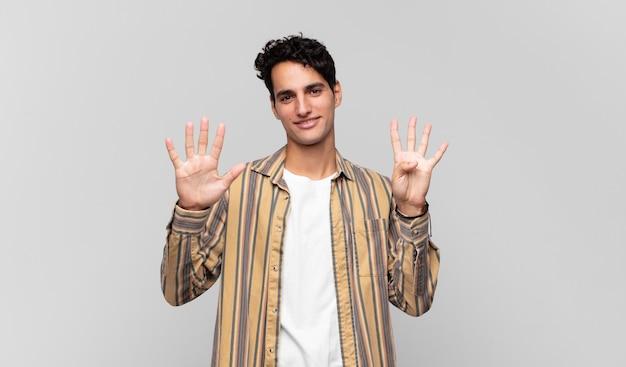 Junger gutaussehender mann, der lächelt und freundlich aussieht, die nummer neun oder neun mit der hand nach vorne zeigt und herunterzählt
