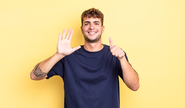 Junger gutaussehender mann, der lächelt und freundlich aussieht, die nummer sechs oder sechs mit der hand nach vorne zeigt und herunterzählt