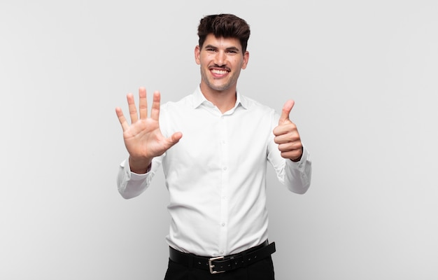 Junger gutaussehender mann, der lächelt und freundlich aussieht, nummer sechs oder sechste mit der hand vorwärts zeigend, countdown