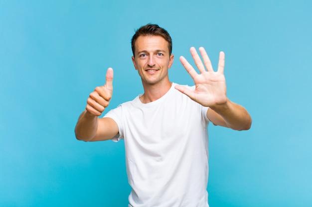 Junger gutaussehender mann, der lächelt und freundlich aussieht, nummer sechs oder sechste mit der hand vorwärts zeigend, herunterzählend