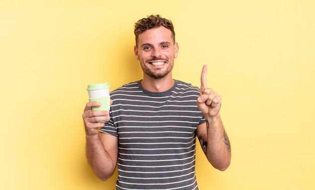 Junger gutaussehender mann, der lächelt und freundlich aussieht und das konzept zum mitnehmen nummer eins zeigt