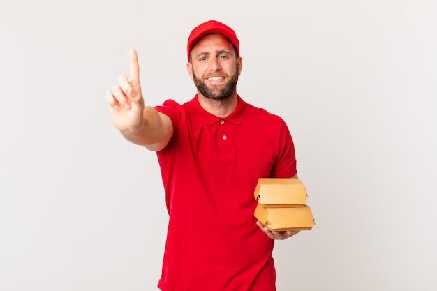 Junger gutaussehender mann, der lächelt und freundlich aussieht und den burger nummer eins zeigt, der das konzept liefert delivering