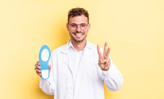 Junger gutaussehender mann, der lächelt und freundlich aussieht und nummer drei zeigt. fußpfleger-konzept