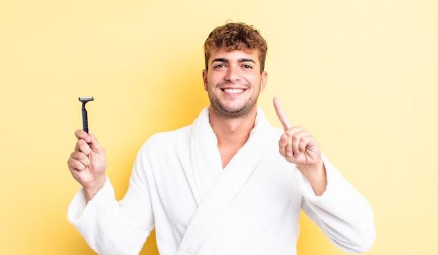 Junger gutaussehender mann, der lächelt und freundlich aussieht und nummer eins zeigt. rasierkonzept