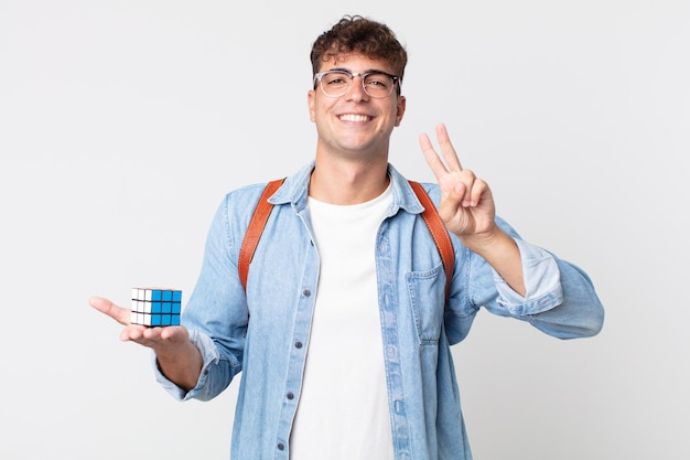 Junger gutaussehender mann, der lächelt und freundlich aussieht und nummer zwei zeigt. intelligenzspielkonzept