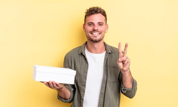 Junger gutaussehender mann, der lächelt und freundlich aussieht und nummer zwei zeigt. white-box-konzept