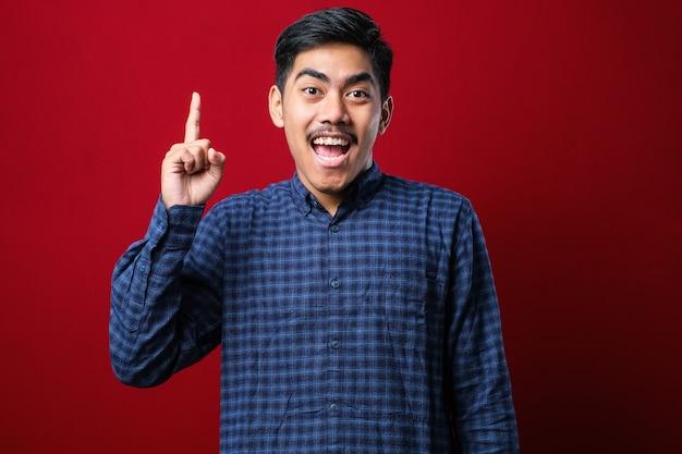 Junger gutaussehender mann, der lässiges hemd über rotem hintergrund trägt und finger mit erfolgreicher idee nach oben zeigt. begeistert und glücklich. nummer eins.