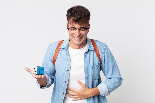 Junger gutaussehender mann, der laut über einen urkomischen witz lacht. intelligenzspielkonzept