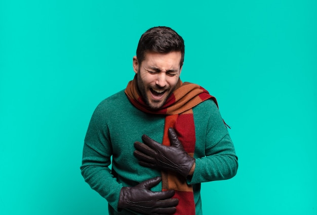 Junger gutaussehender mann, der laut über einen urkomischen witz lacht, sich glücklich und fröhlich fühlt und spaß hat. kälte- und winterkonzep