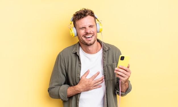 Junger gutaussehender mann, der laut über einige urkomische witzkopfhörer und smartphone-konzept lacht