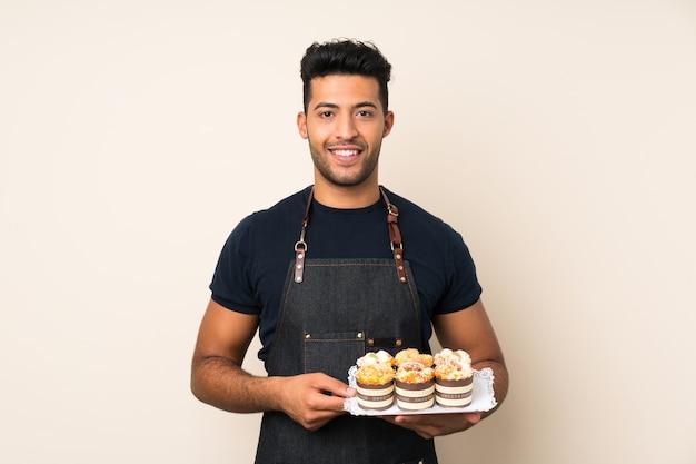 Junger gutaussehender mann, der minikuchen hält
