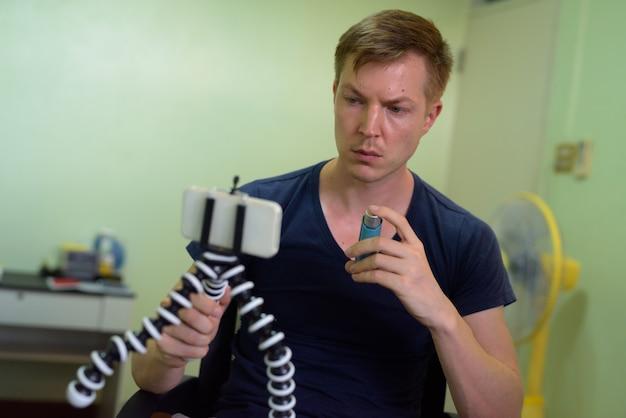 Junger gutaussehender mann, der mit asthmainhalator zu hause vloggt