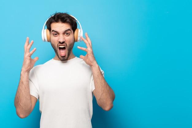 Junger gutaussehender mann, der mit den händen in der luft schreit und sich wütend, frustriert, gestresst und verärgert fühlt