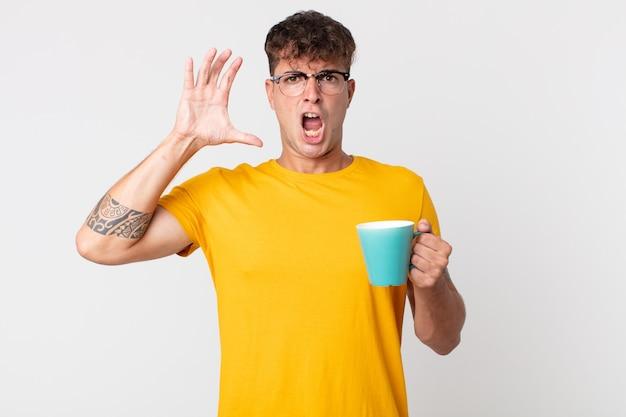 Junger gutaussehender mann, der mit den händen in die luft schreit und eine kaffeetasse hält